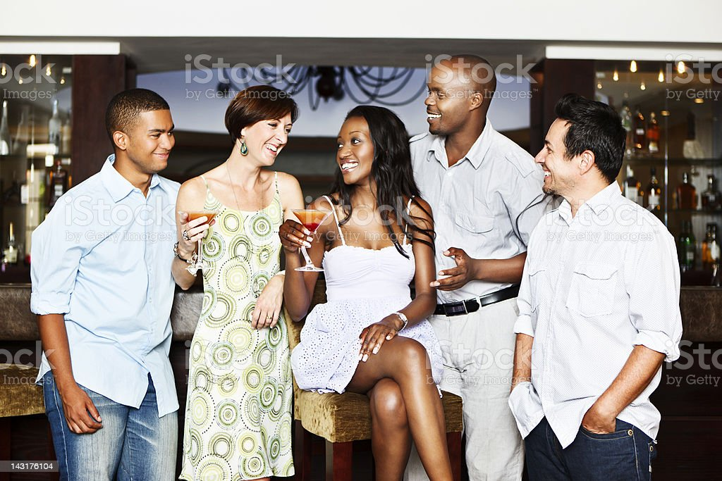 Mixed group of smiling young adults drinking cocktails at bar royalty-free stock photo