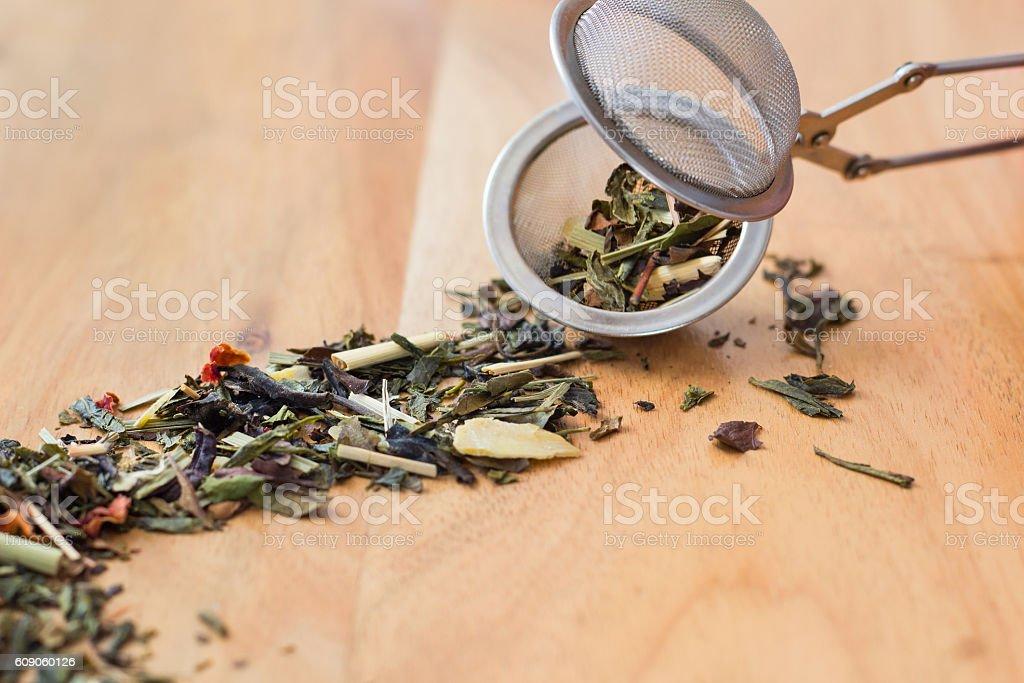 Mixed herbal tea in an open tea strainer on wood stock photo