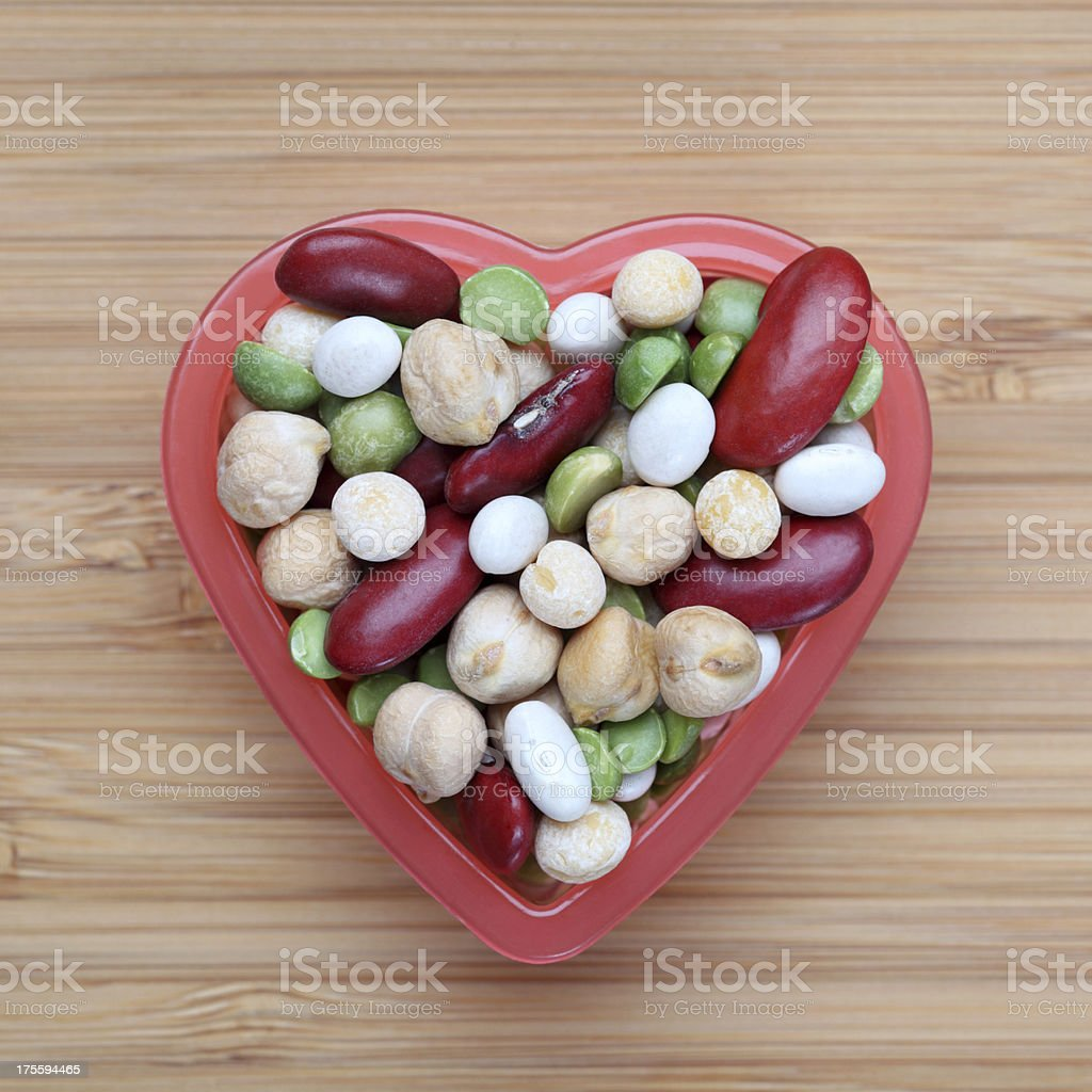 Mixed legume beans in a heart bowl stock photo