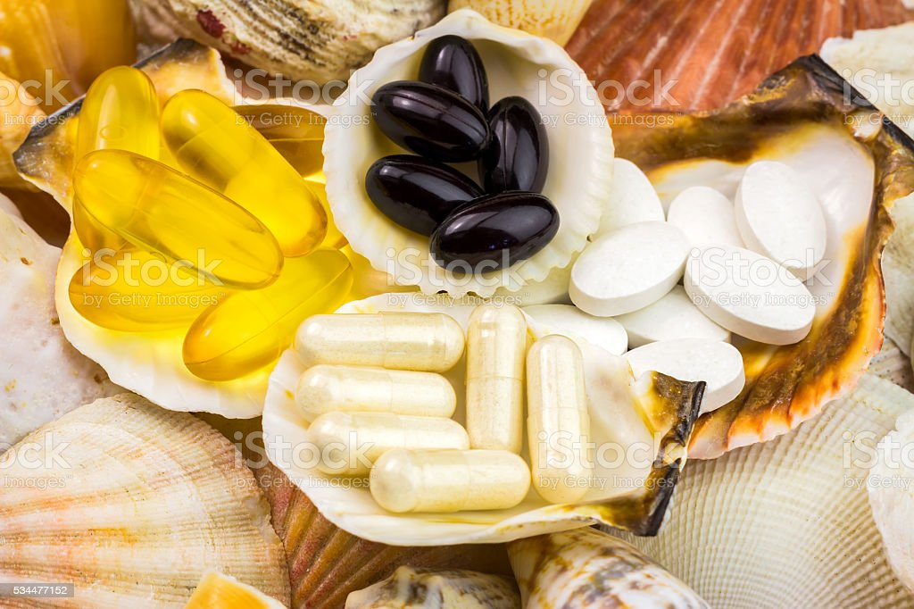 Mixed natural food supplement pills on the beautiful seashells background stock photo