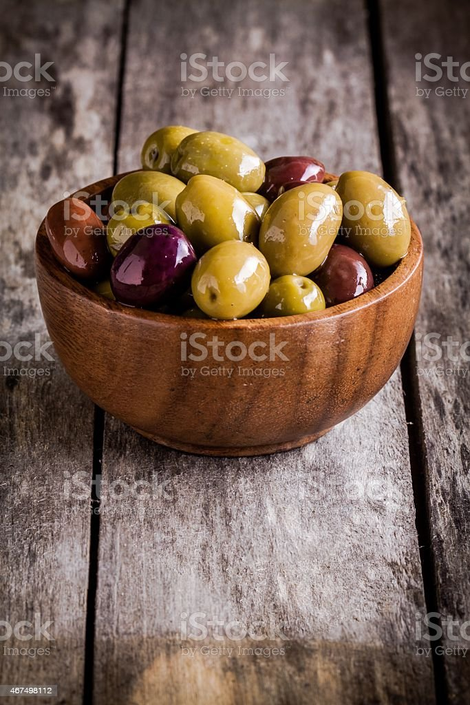 mixed olives in a bowl on a rustic table stock photo