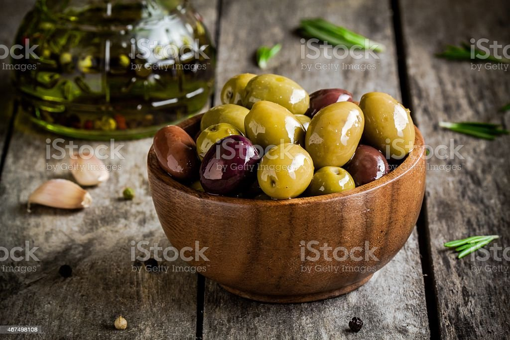 mixed olives in bowl with rosemary, olive oil and garlic stock photo