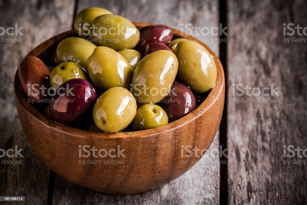 mixed olives in wooden bowl closeup on a rustic table stock photo