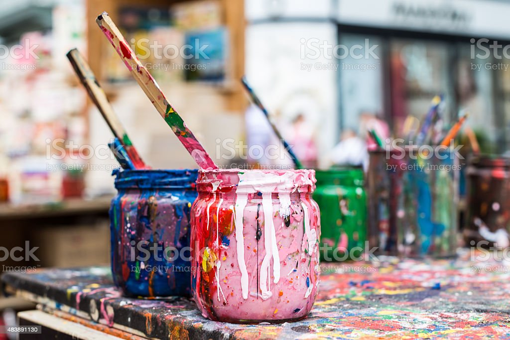 Mixed paint containers on a messy table. stock photo