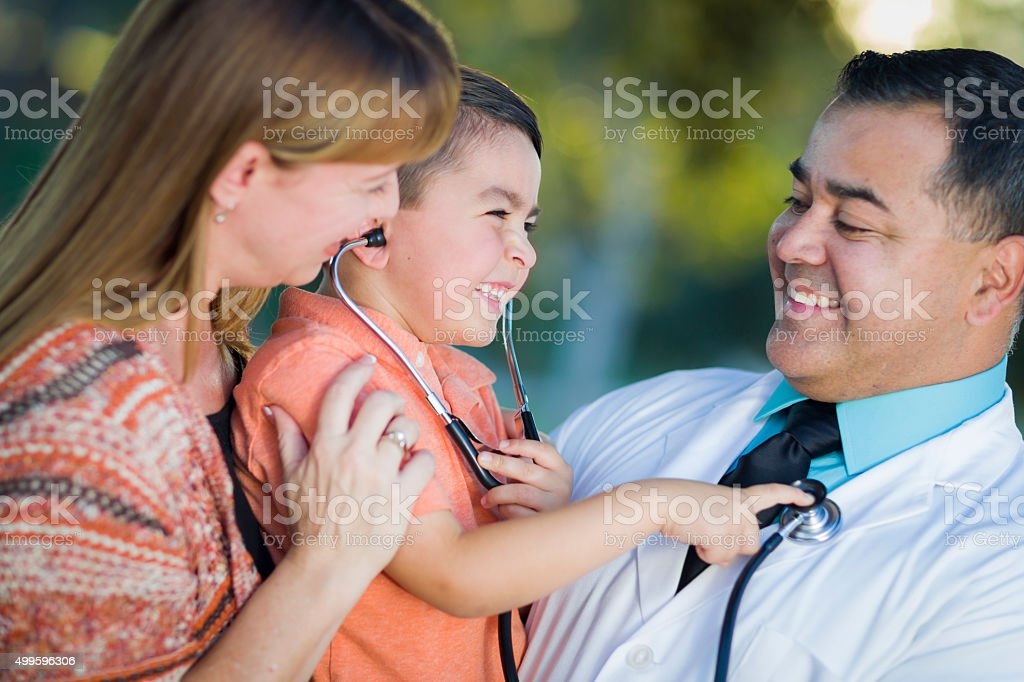 Mixed Race Boy, Mother and Doctor Having Fun With Stethoscope stock photo