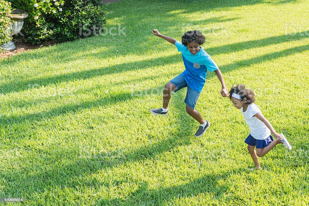 Mixed race brother and sister playing in park stock photo