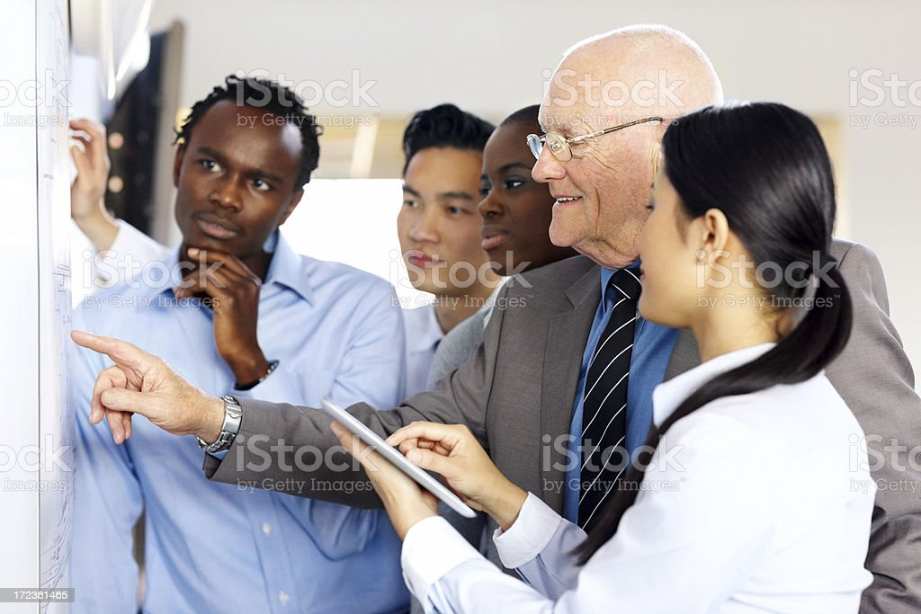 Mixed race businesspeople discussing new building plan royalty-free stock photo