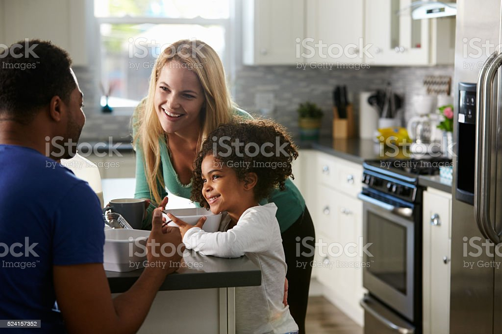 Mixed race couple and daughter talk together in the kitchen stock photo
