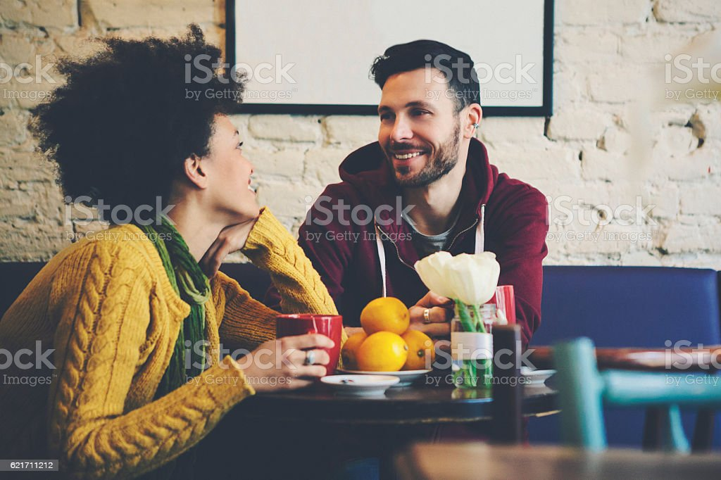 Mixed race couple at coffee house having coffee and chatting stock photo