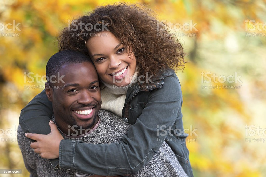 Mixed Race Couple Giving Each Other Piggy Backs stock photo
