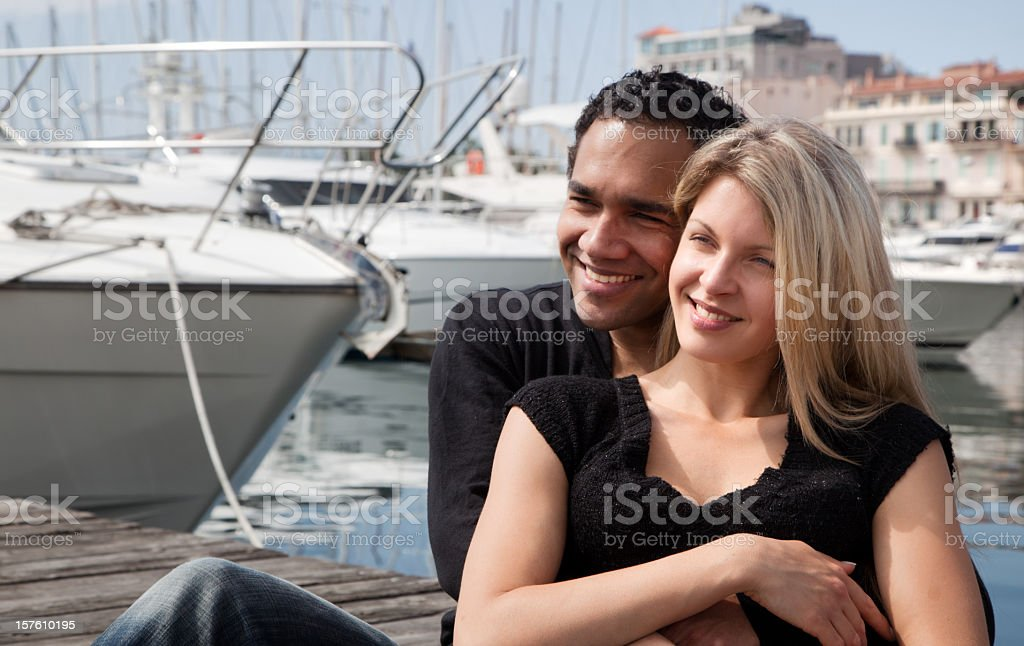 Mixed race couple hugging and smiling in marina, Cannes, France royalty-free stock photo