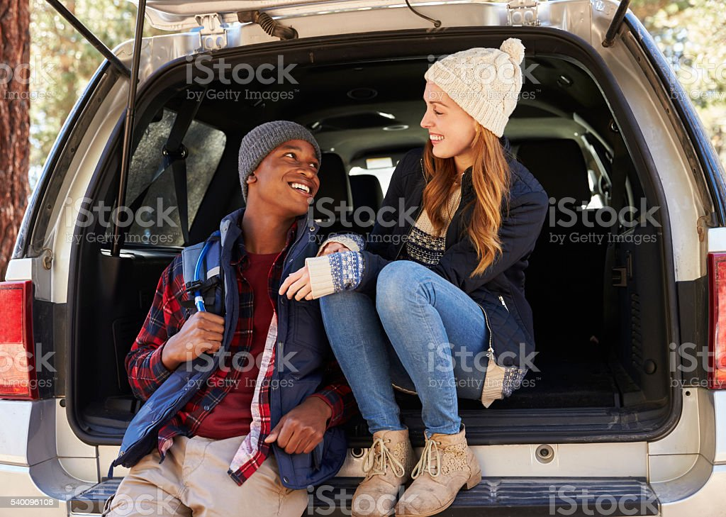 Mixed race couple in open back of car looking at each stock photo