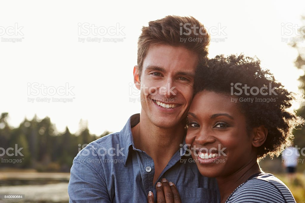 Mixed race couple in the countryside, looking to camera stock photo
