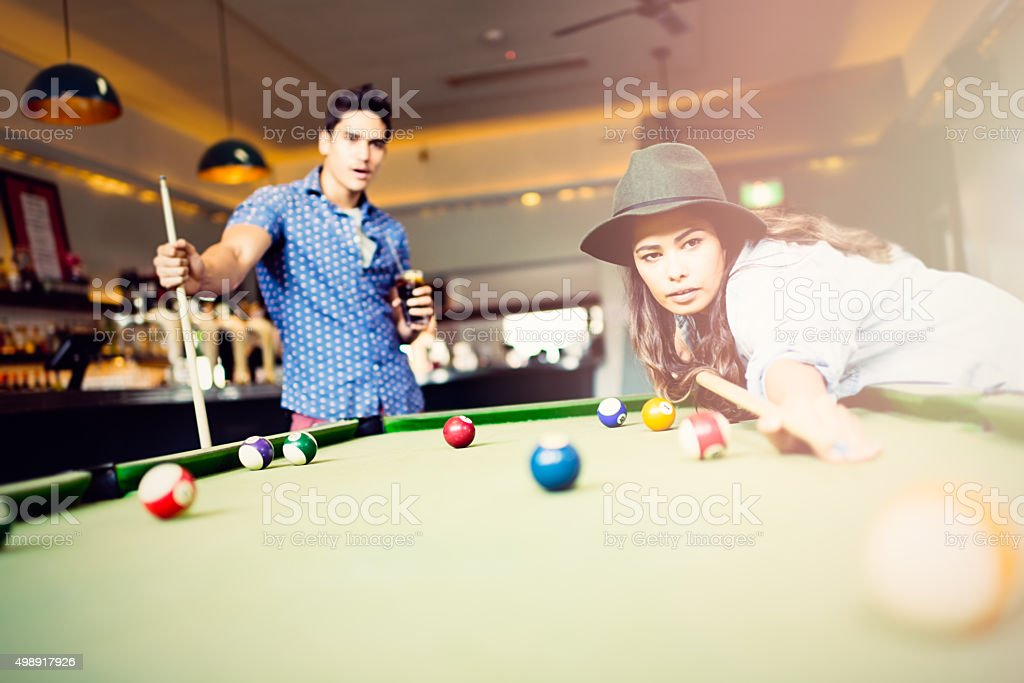 Mixed race couple playing pool game in pub stock photo