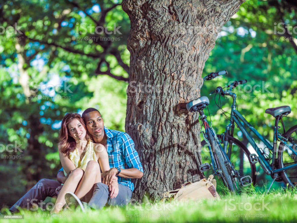 Mixed race couple relaxing in Central Park, New York stock photo