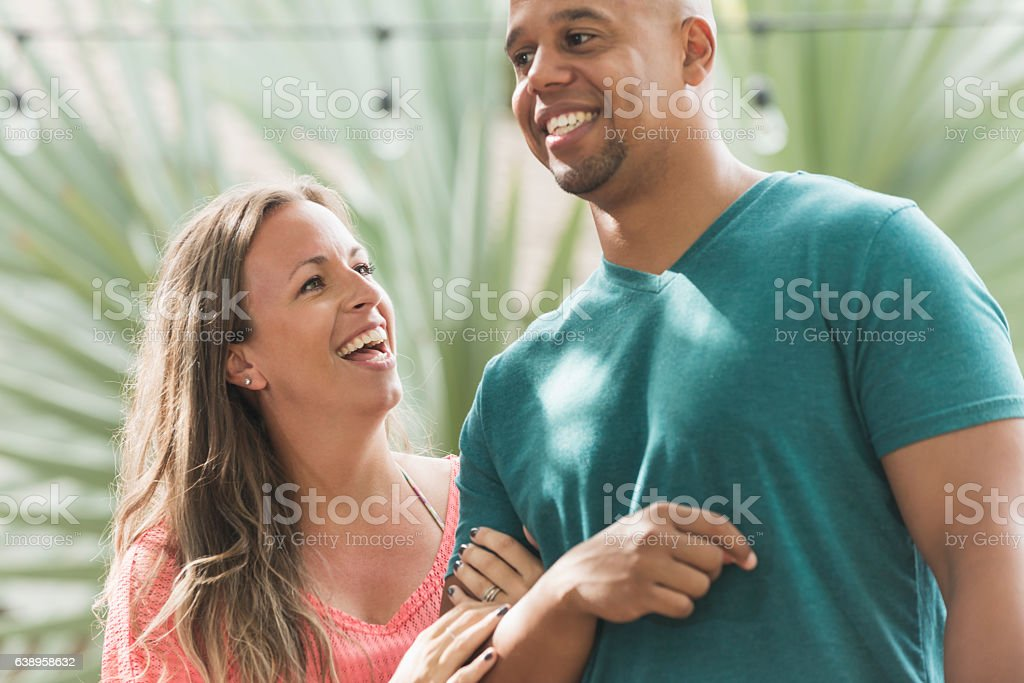 Mixed race couple, woman laughing stock photo