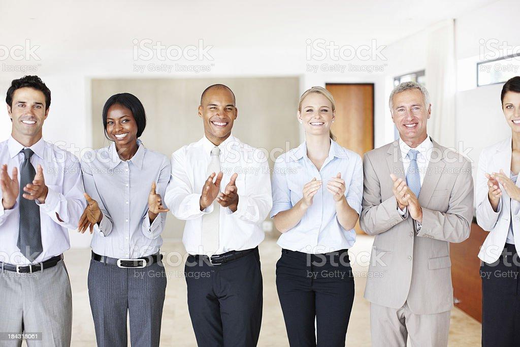 Mixed race executives applauding royalty-free stock photo