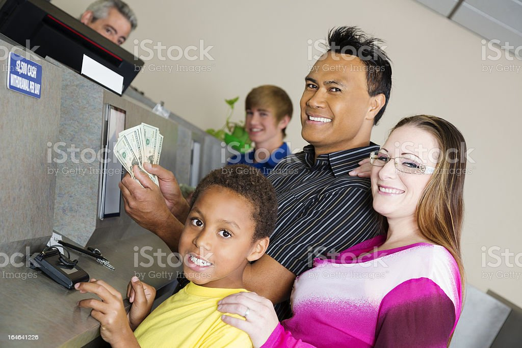 Mixed race family getting money at the bank royalty-free stock photo