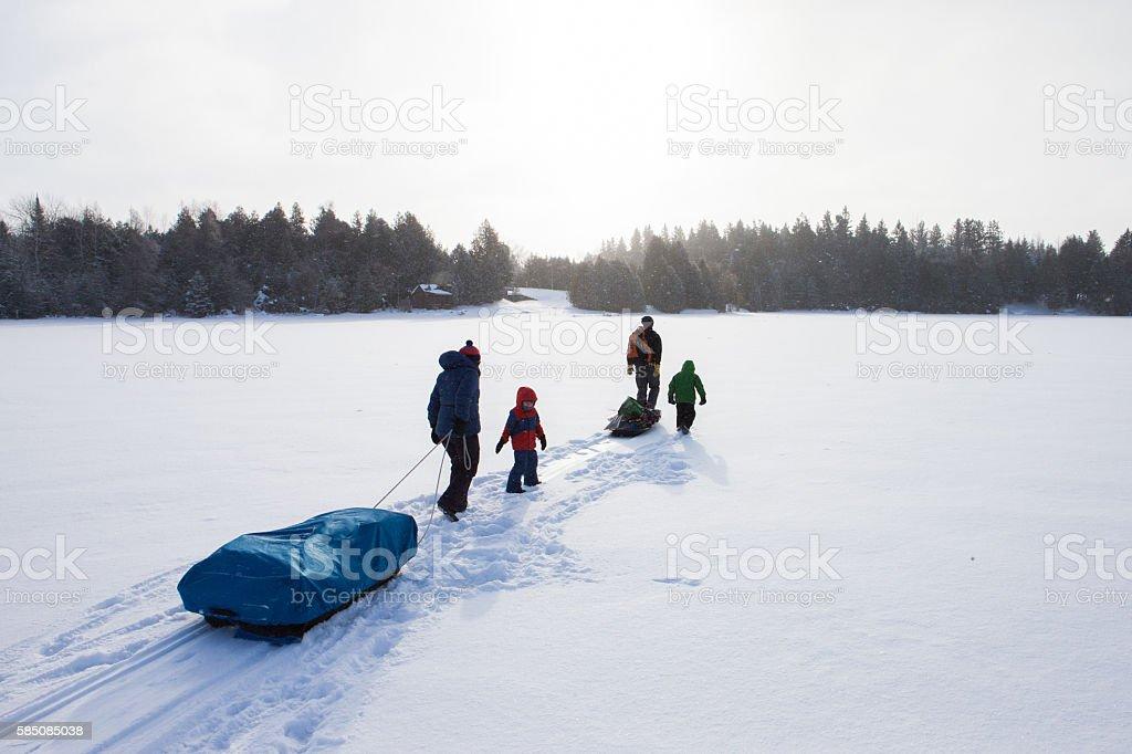 Mixed race family going ice fishing stock photo