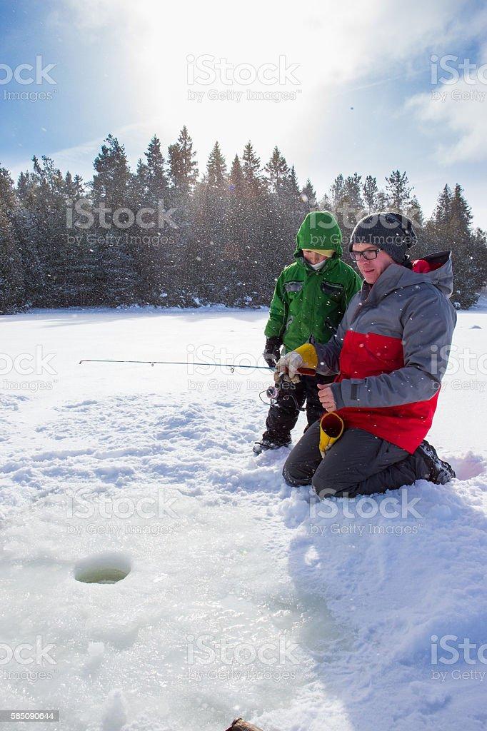 Mixed race family ice fishing stock photo