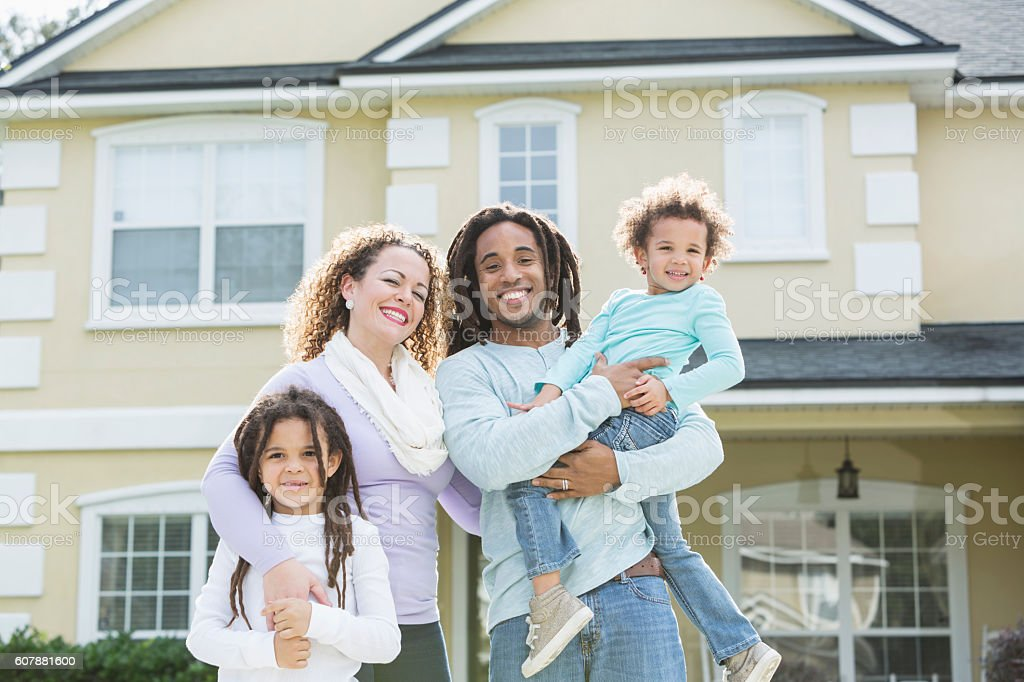 Mixed race family of four in front of home stock photo