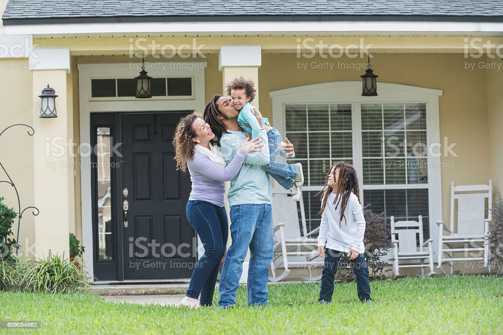 Mixed race family playing in front yard of home stock photo