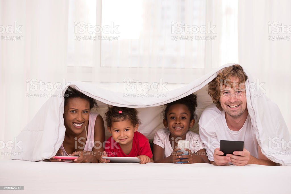 Mixed race family with electronic devices under blanket in bed. stock photo