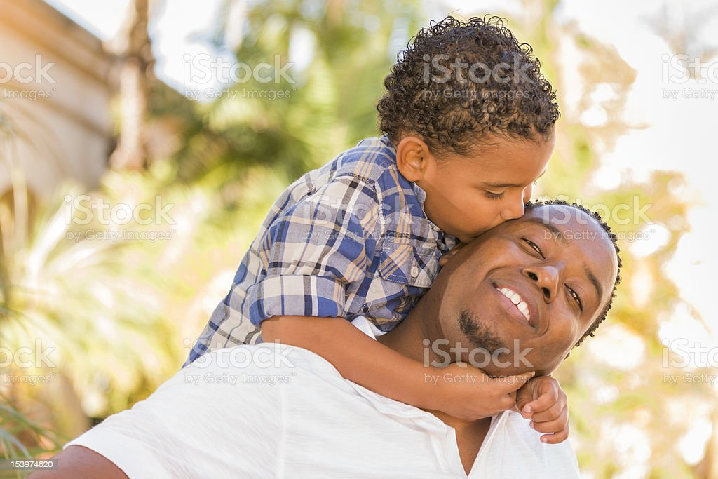 Mixed Race Father and Son Playing Piggyback in Park royalty-free stock photo