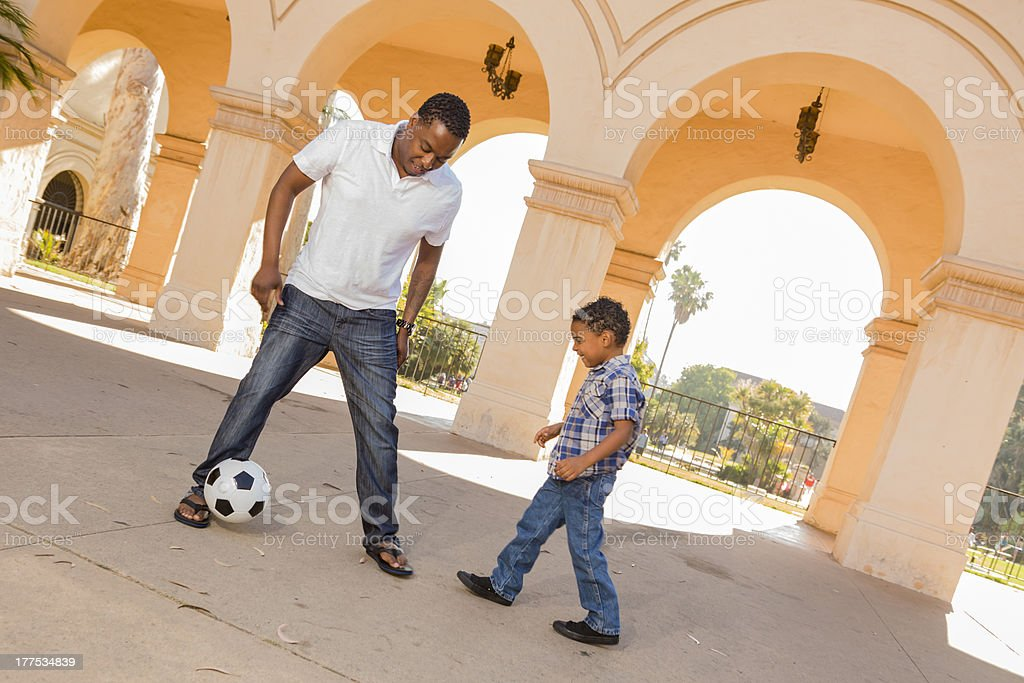 Mixed Race Father and Son Playing Soccer in the Courtyard royalty-free stock photo