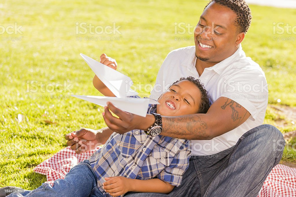 Mixed Race Father and Son Playing with Paper Airplanes royalty-free stock photo