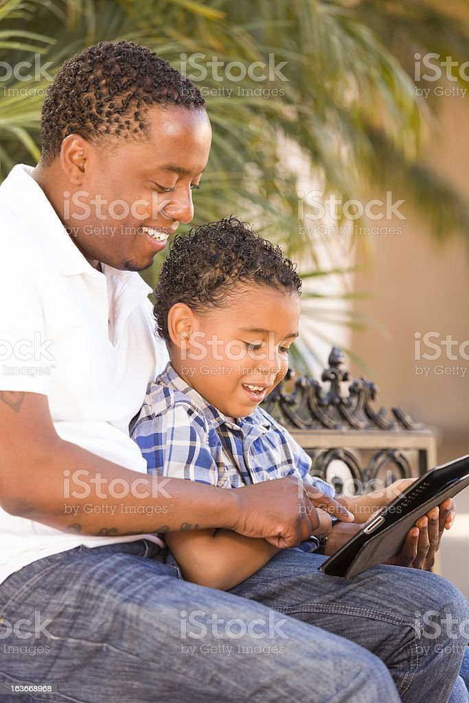 Mixed Race Father and Son Using Touch Pad Computer Tablet stock photo