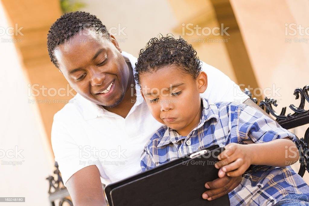 A mixed race father teaching his son how to use a tablet royalty-free stock photo