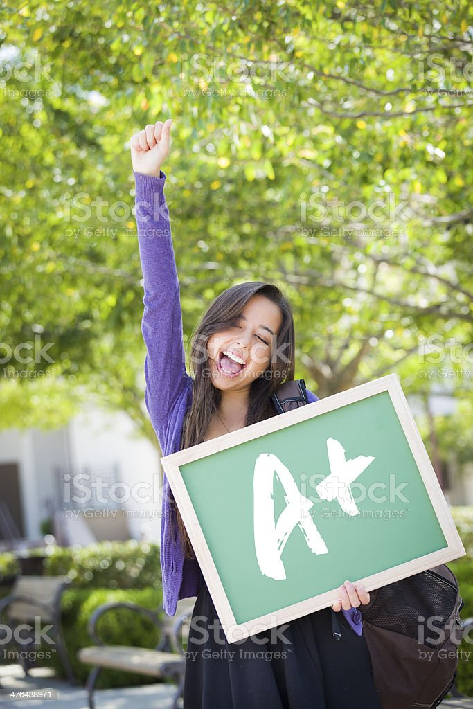 Mixed Race Female Student Holding Chalkboard With A+ Written stock photo