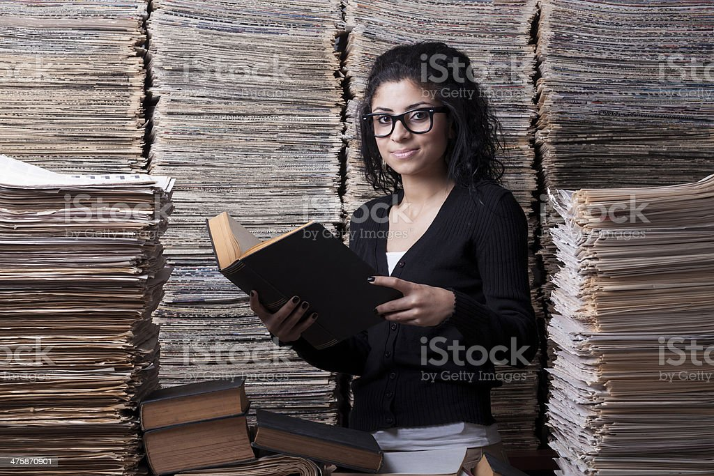 Mixed race female student reading book in library stock photo