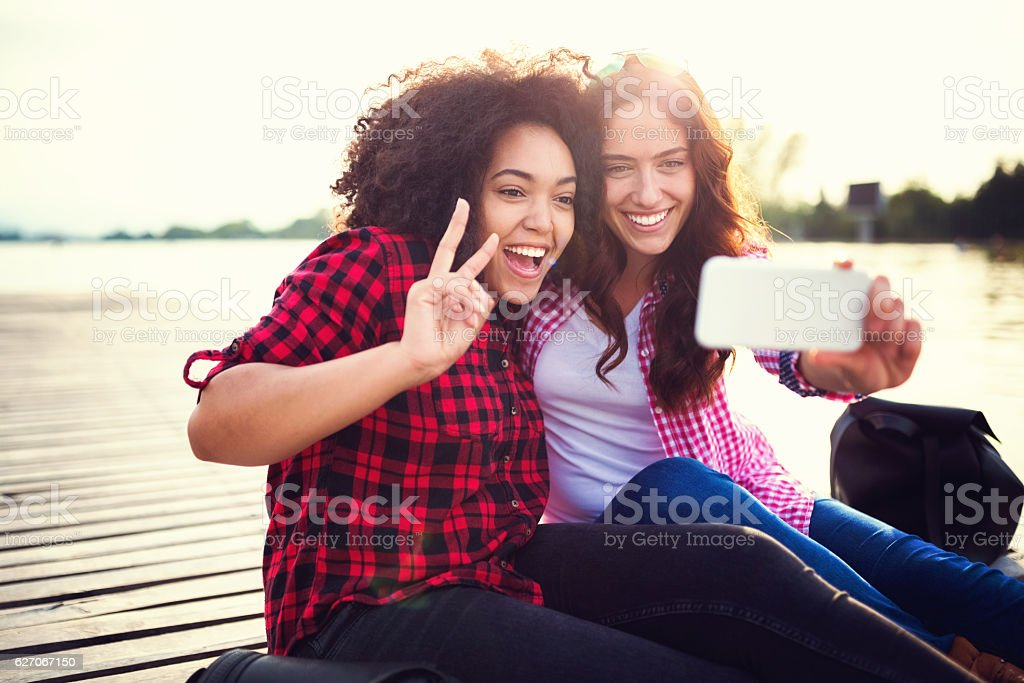 Mixed race friends taking selfie together stock photo