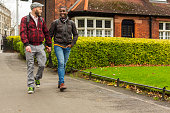 Mixed Race Gay Couple Walking in a Public Park