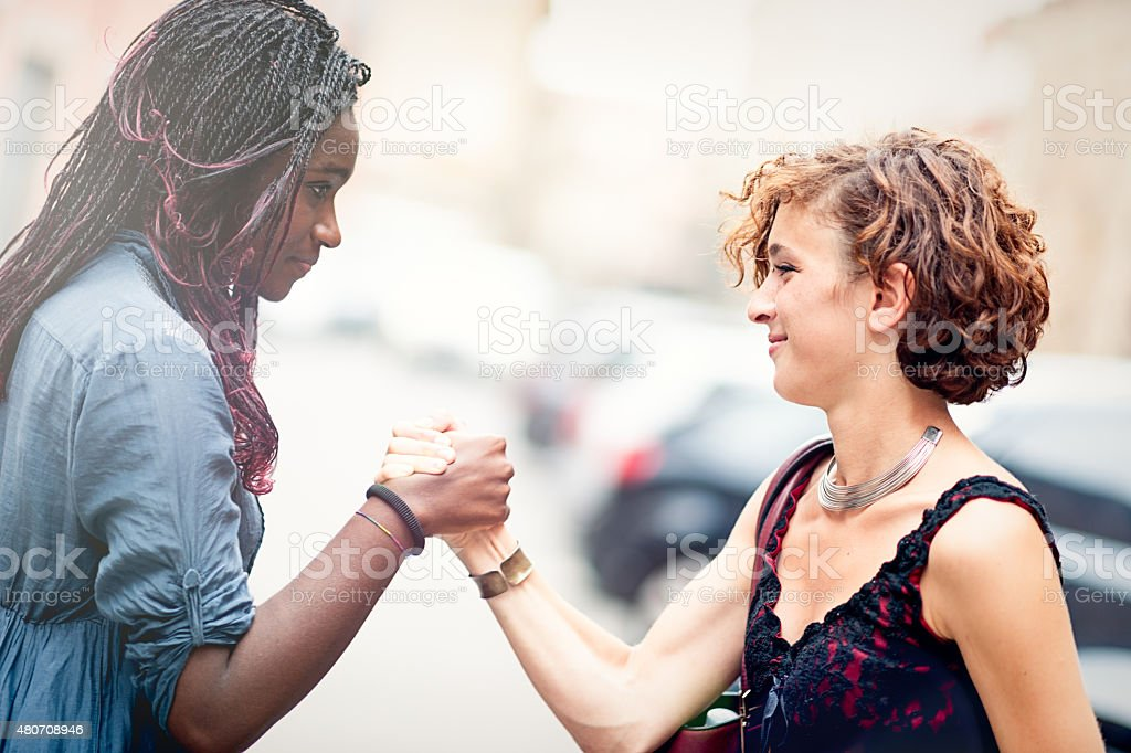 Mixed race girlfriends making a sign of forgiveness stock photo