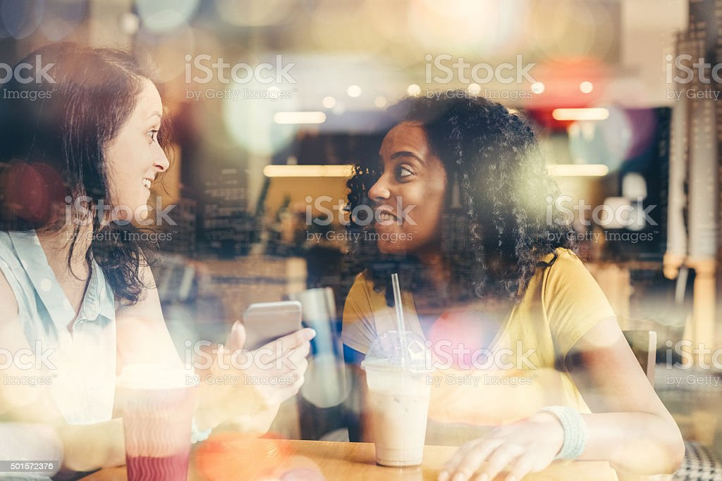 Mixed race girls at coffee break stock photo