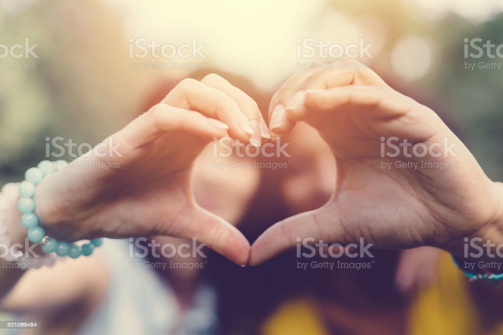 Mixed race girls making heart symbol with hands stock photo