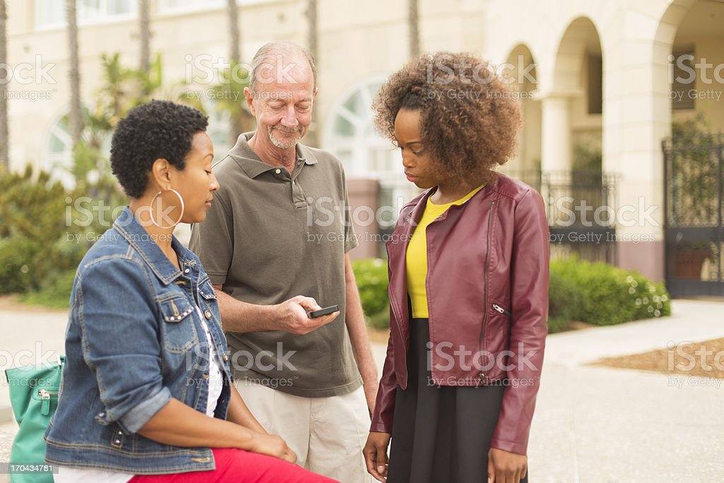 Mixed Race Group Looking at a Phone stock photo