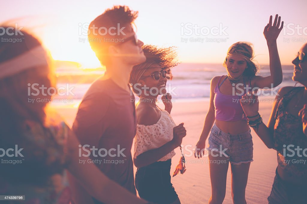 Mixed race group of friends dancing together at a beachparty stock photo
