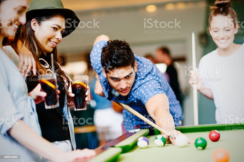 Mixed race group of friends playing pool game in pub stock photo