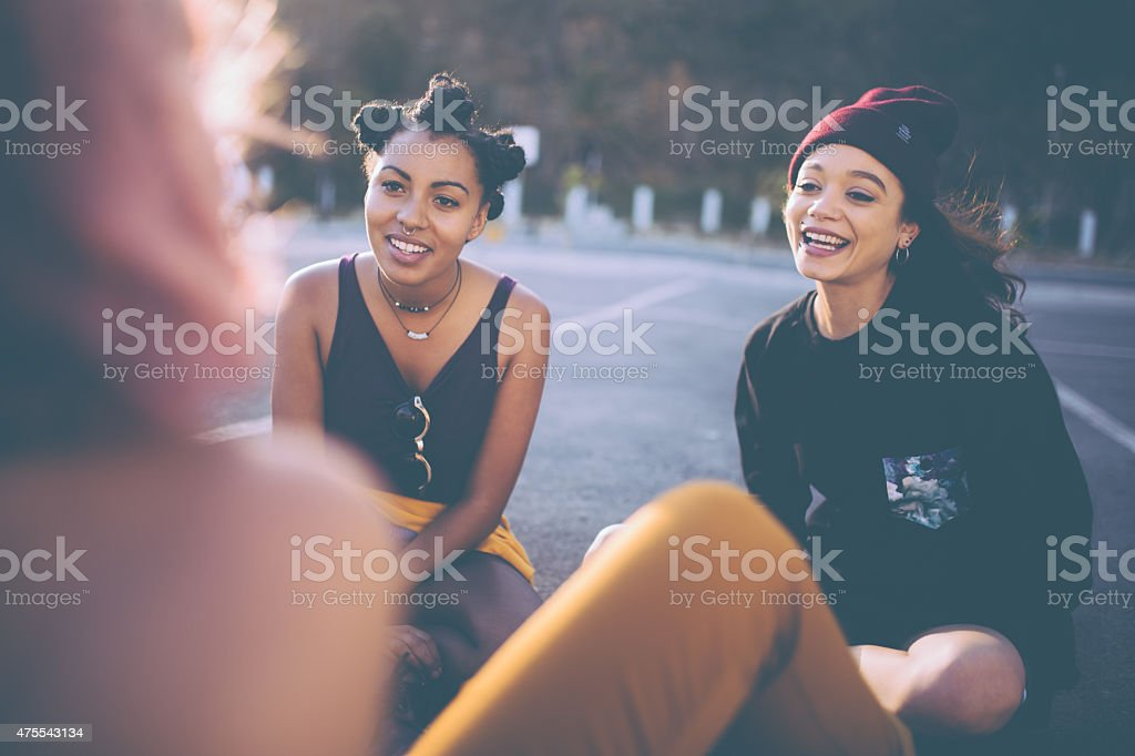 Mixed race group of teen grunge girls talking outside stock photo