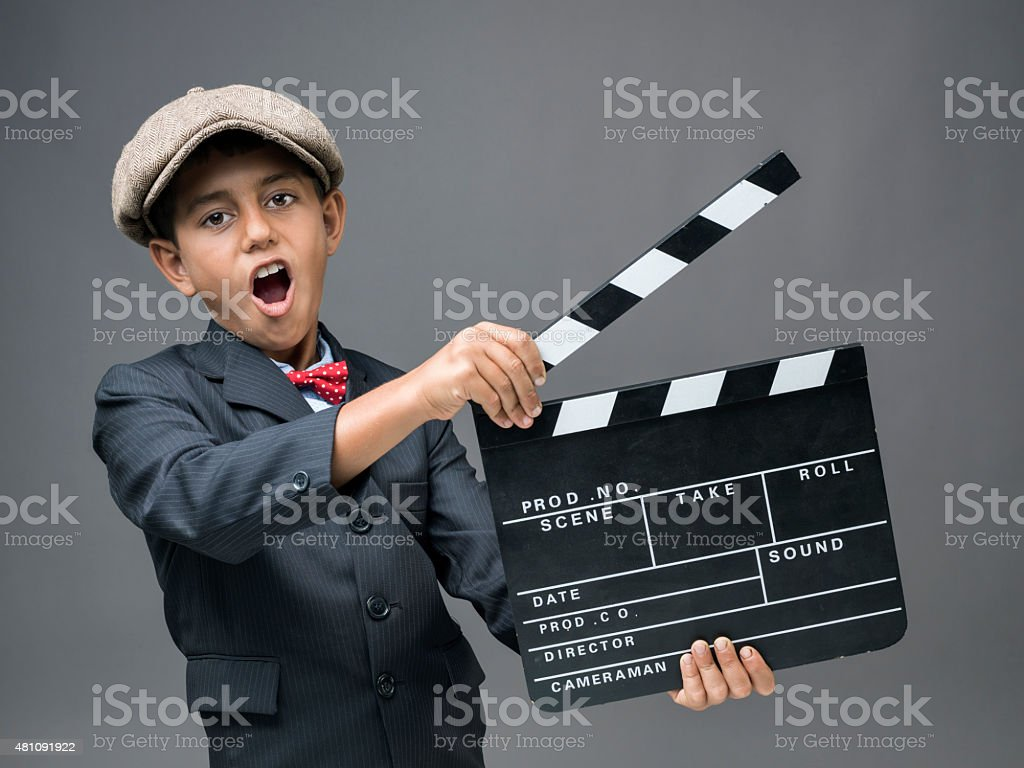 Mixed race little boy holding film slate and shouting stock photo