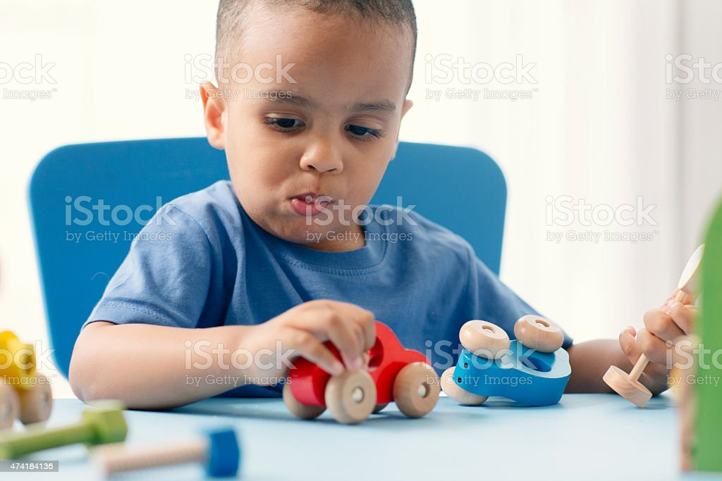 Mixed Race Little boy playing with toy car, eating biscuit. stock photo