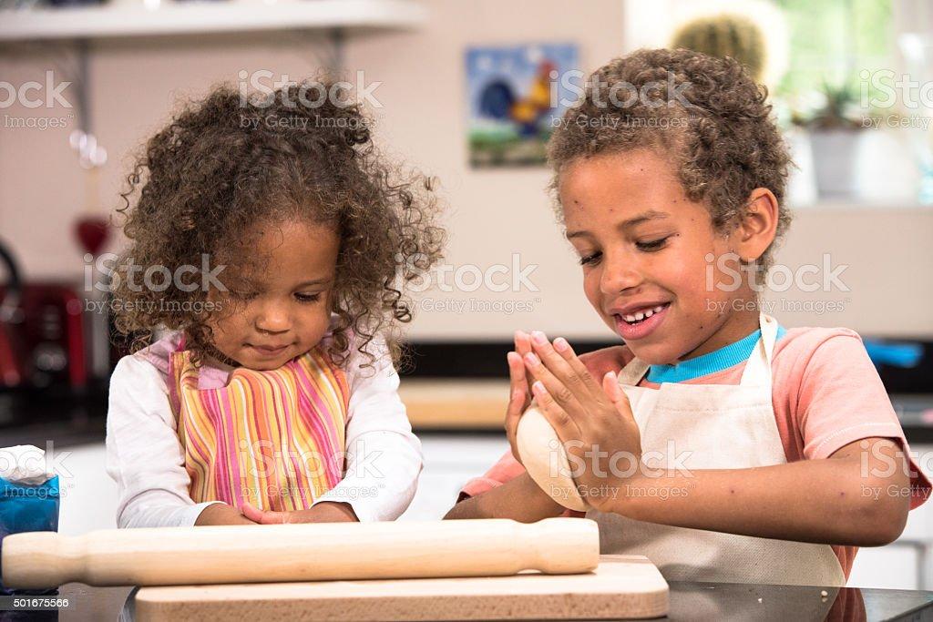 Mixed Race Little Girl And Boy Preparing Dough stock photo