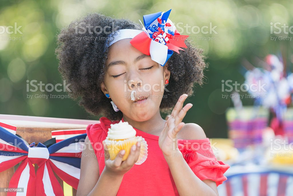 Mixed race little girl having cupcake on 4th of July stock photo