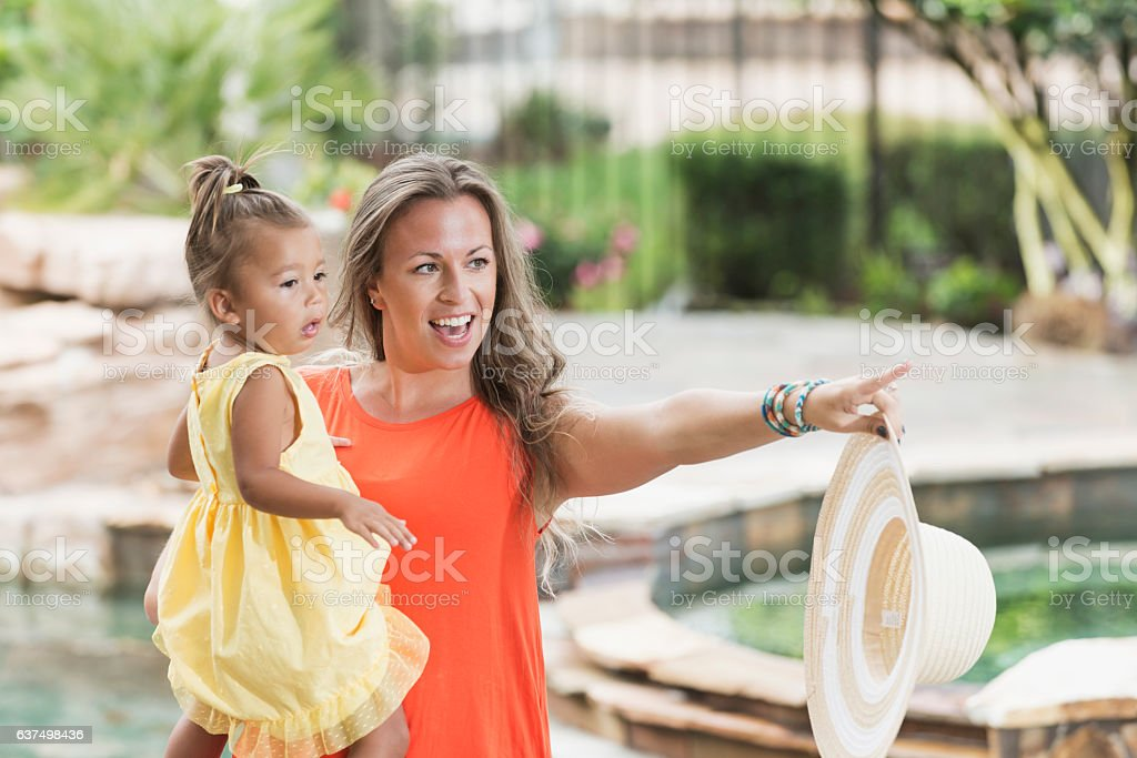 Mixed race mother and little girl watching, pointing stock photo