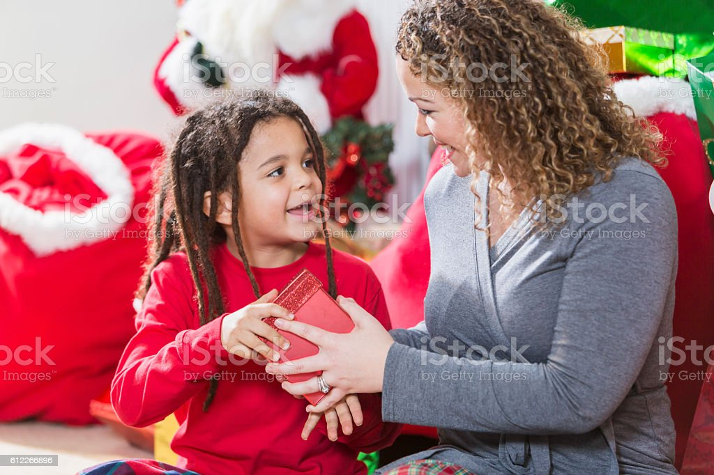 Mixed race mother giving gift to son at Christmas stock photo
