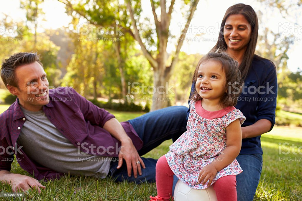 Mixed race parents and young daughter sit in park, stock photo